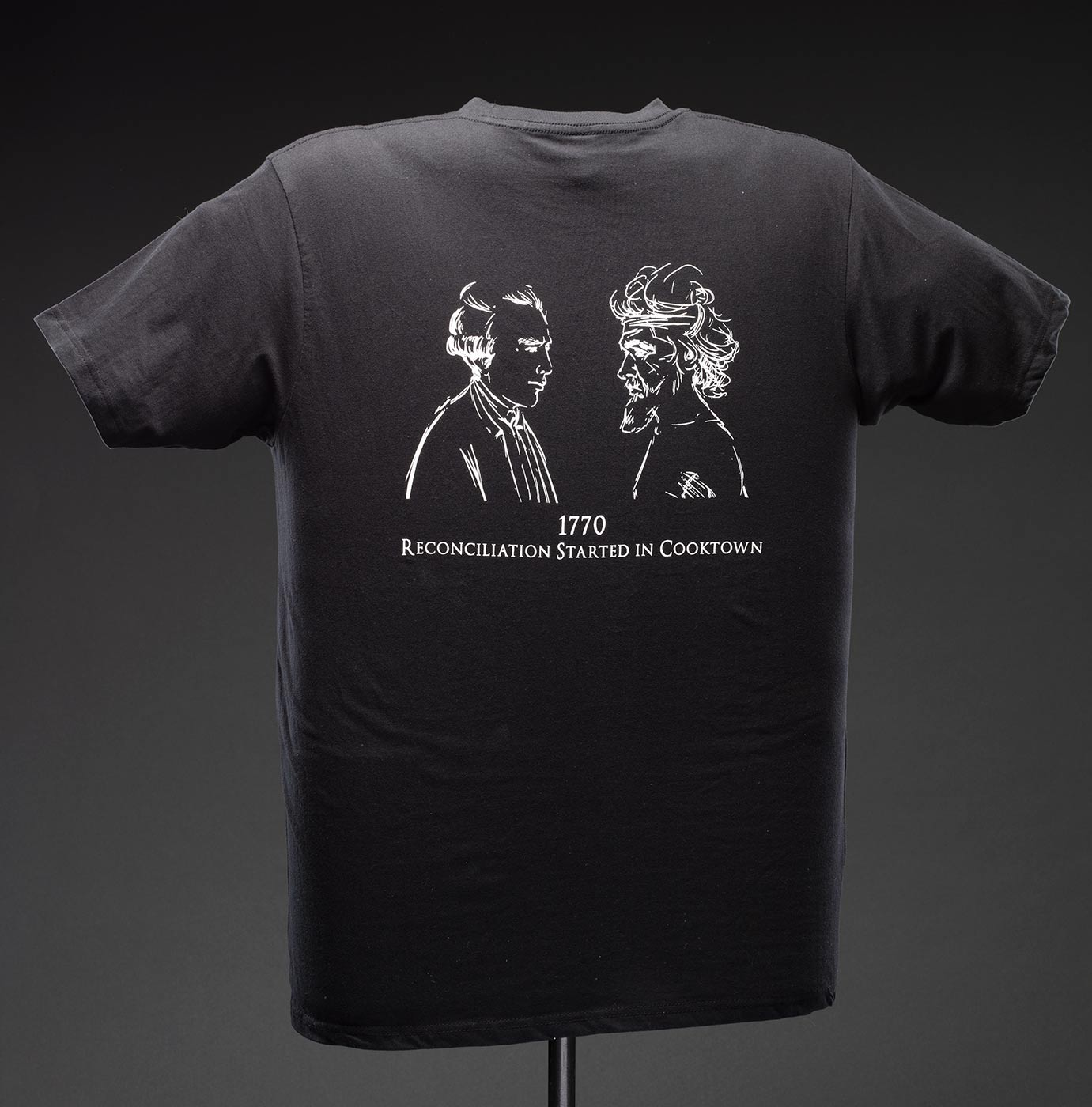 A black t-shirt with white text on the front that reads ?Hopevale / Arts & Culture Centre?. On the reverse there is a white printed illustration of two men facing each other with ?1770 / RECONCILIATION STARTED IN COOKTOWN? printed beneath it.