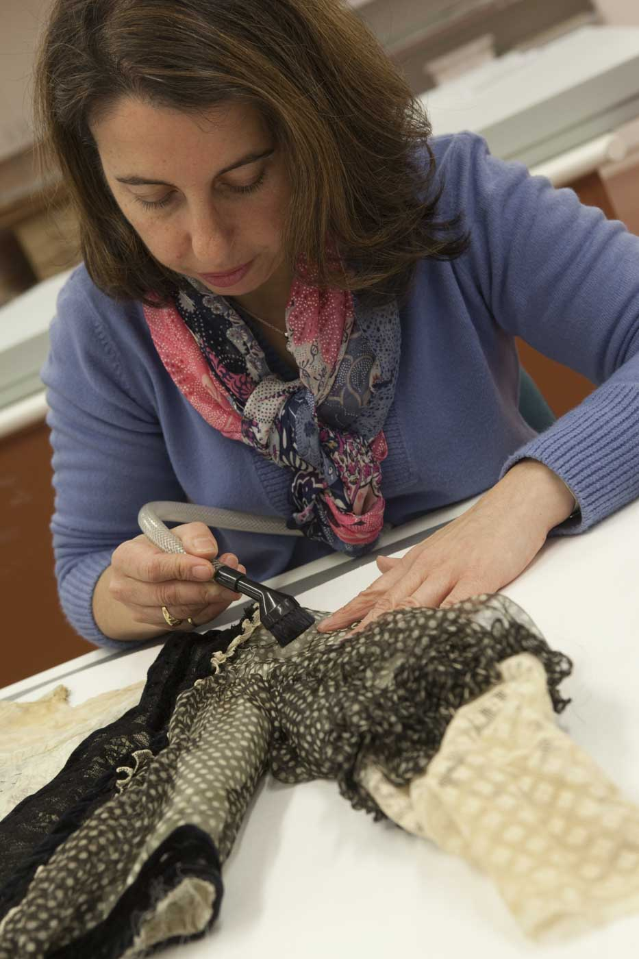 Conservator brush-vacuuming a sleeve on the dress. - click to view larger image