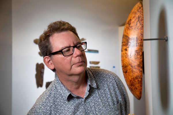 Curator Ian Coates examines a shield mounted on a wall.