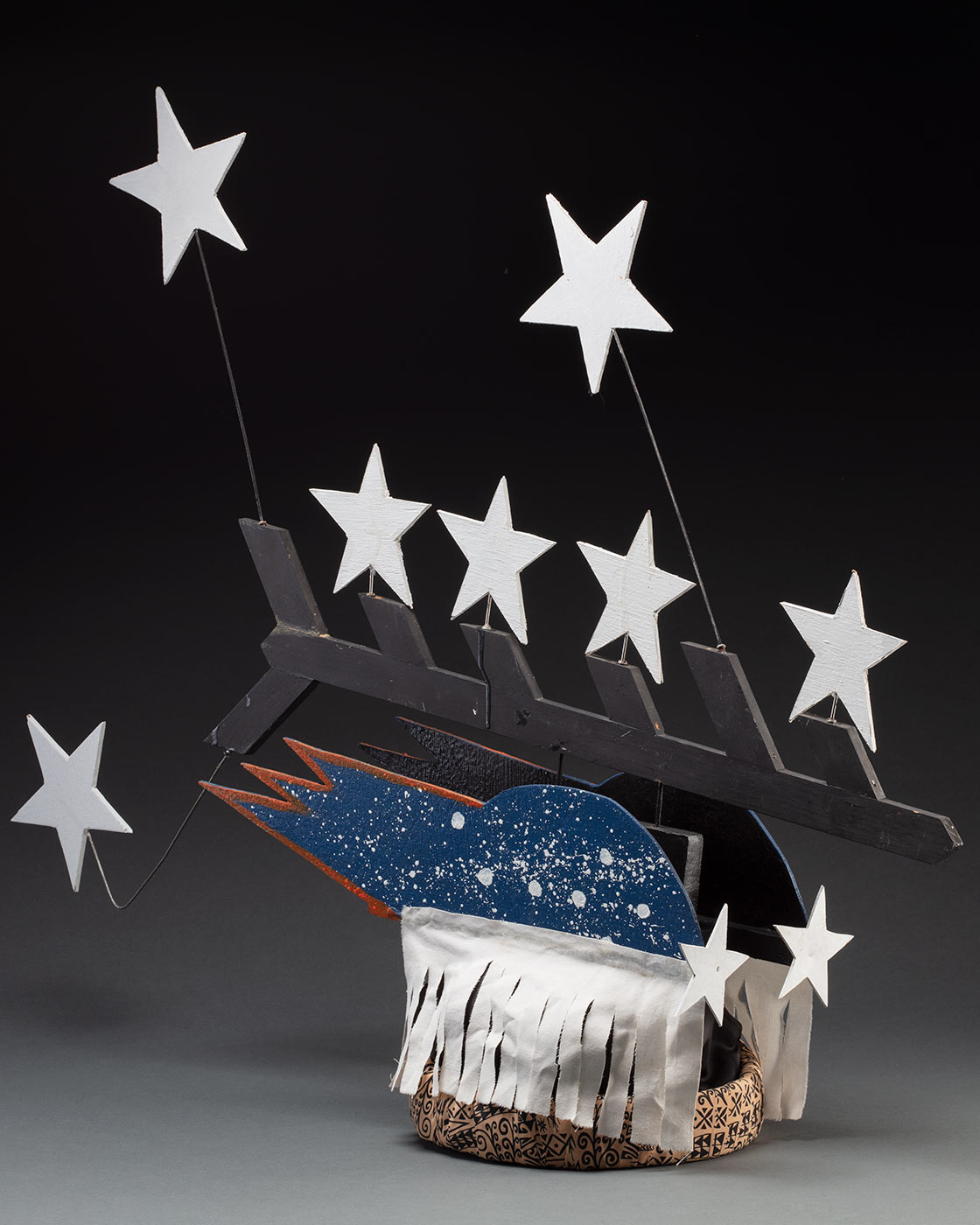 A headdress featuring seven stars protruding from a black painted piece of board forming half a fishbone pattern. It is connected to two pieces of board painted blue with white splatter and seven stars on each side with a white fabric fringe at the bottom. It is all attached to a fabric wrapped headband in the centre.
