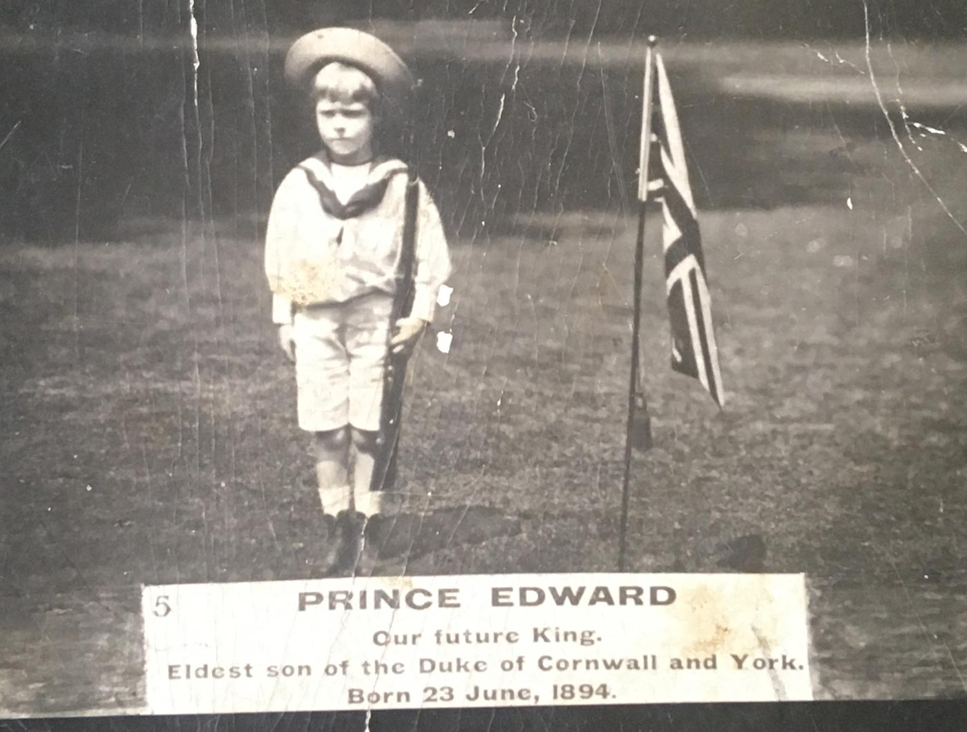 Black and white postcard featuring a young boy holding a gun with the British flag to the right of him. There is a label with the text: PRINCE EDWARD / OUR FUTURE KING. - click to view larger image