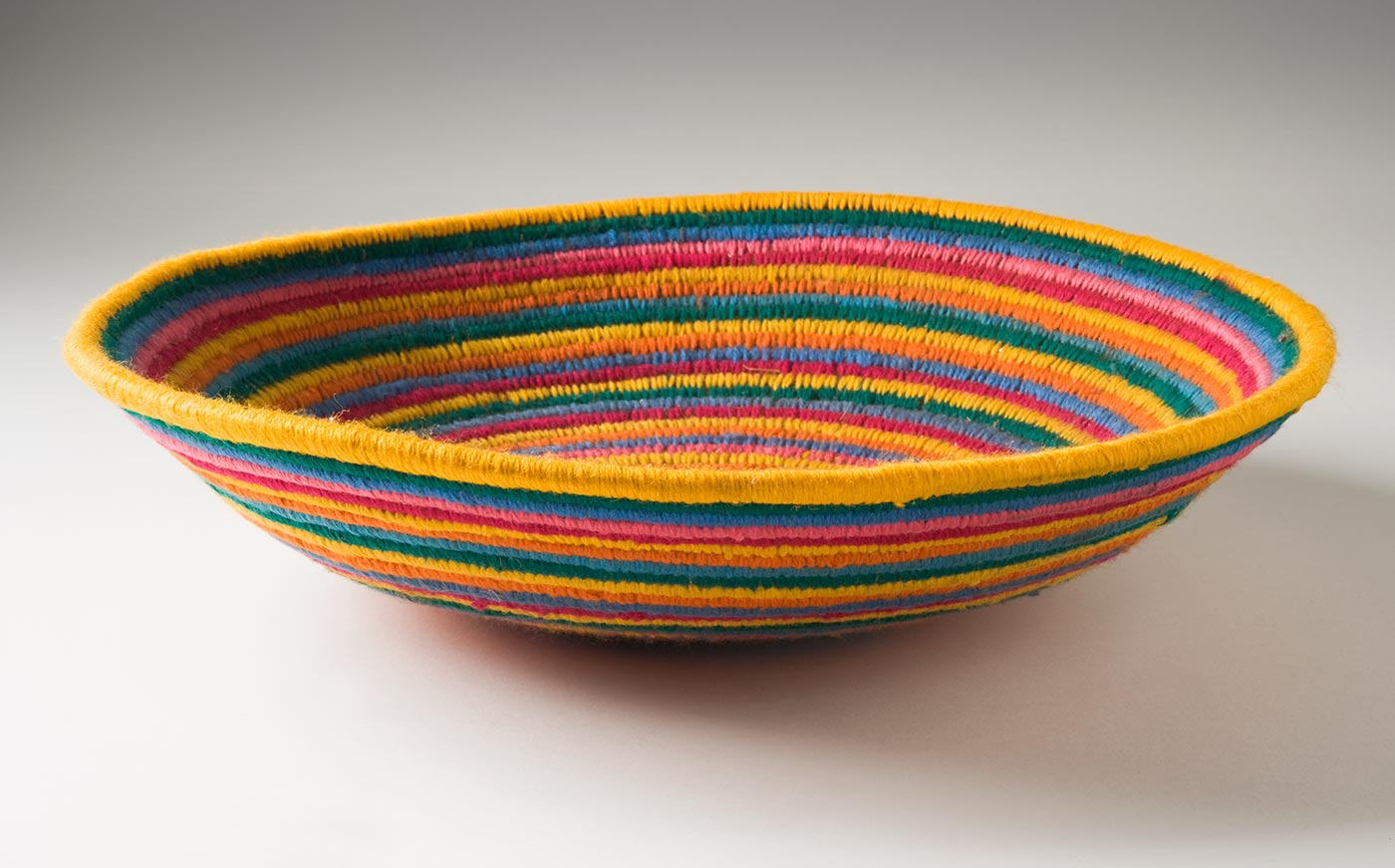 A multi-coloured circular coiled bowl-shaped basket made of yarn and plant fibre. The centre of the basket is in green yarn followed by horizontal stripes of yarn in purple, blue, pink, dark pink, orange and yellow. - click to view larger image