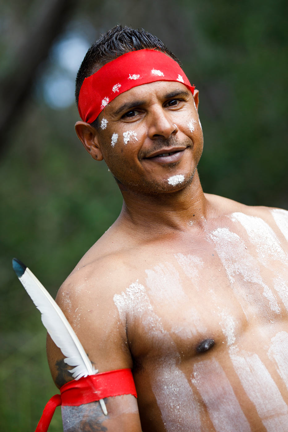 Colour photograph of a man smiling and posing for the camera . He is wearing a red bandana and body paint. - click to view larger image
