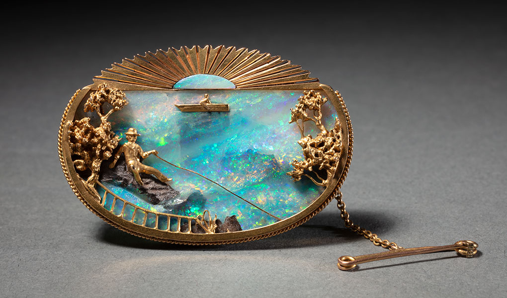 An oval gold set brooch with a plaque of boulder opal depicting a lake fishing scene. - click to view larger image