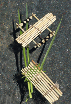 A colour image of a hand-craft raft model made from bamboo and twine