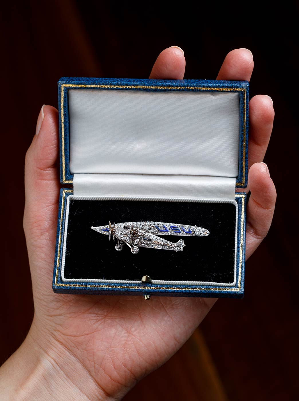 A diamond and platinum brooch in the shape of a plane. - click to view larger image