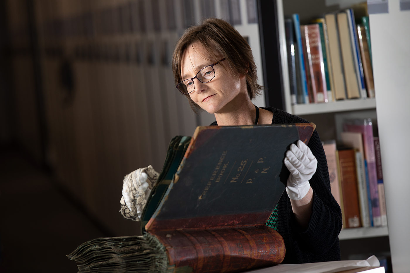 Colour photograph of a woman wearing conservation gloves and studying lace samples from a large leather-bound book. - click to view larger image