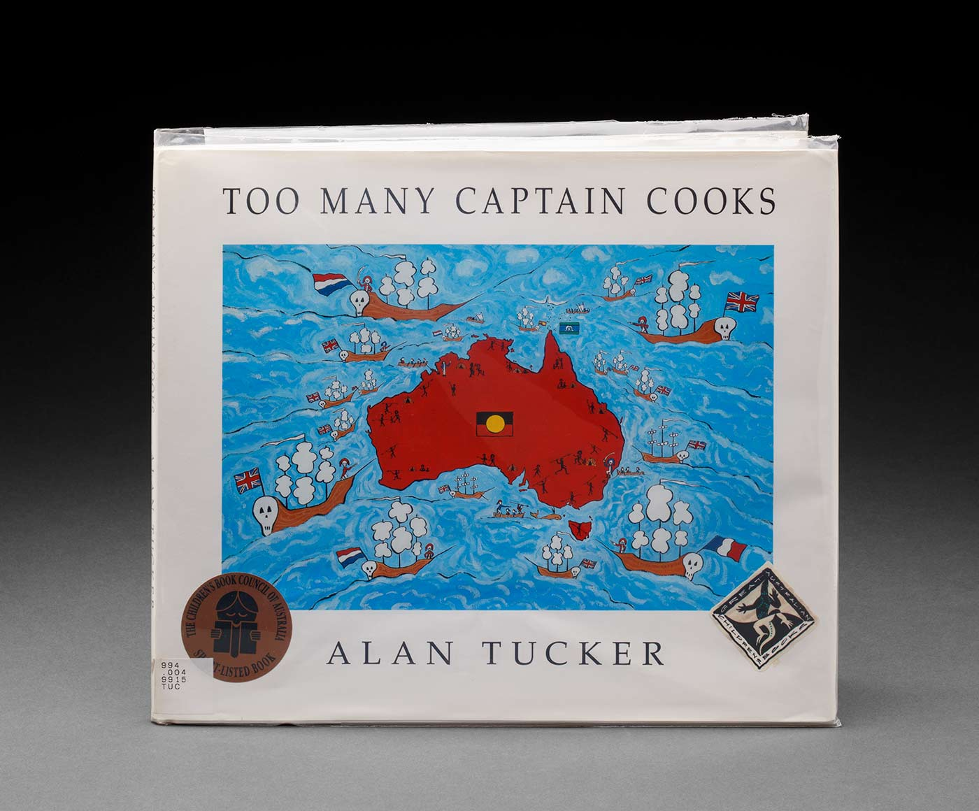 A hard cover children's book titled 'TOO MANY CAPTAIN COOKS' by 'ALAN TUCKER'. The cover features a map of Australia in red surrounded by blue water with a white boarder. There are boats with skulls at one end on the water around Australia and figures around the edge of Australia holding spears. There is an Aboriginal flag in the centre of Australia. - click to view larger image