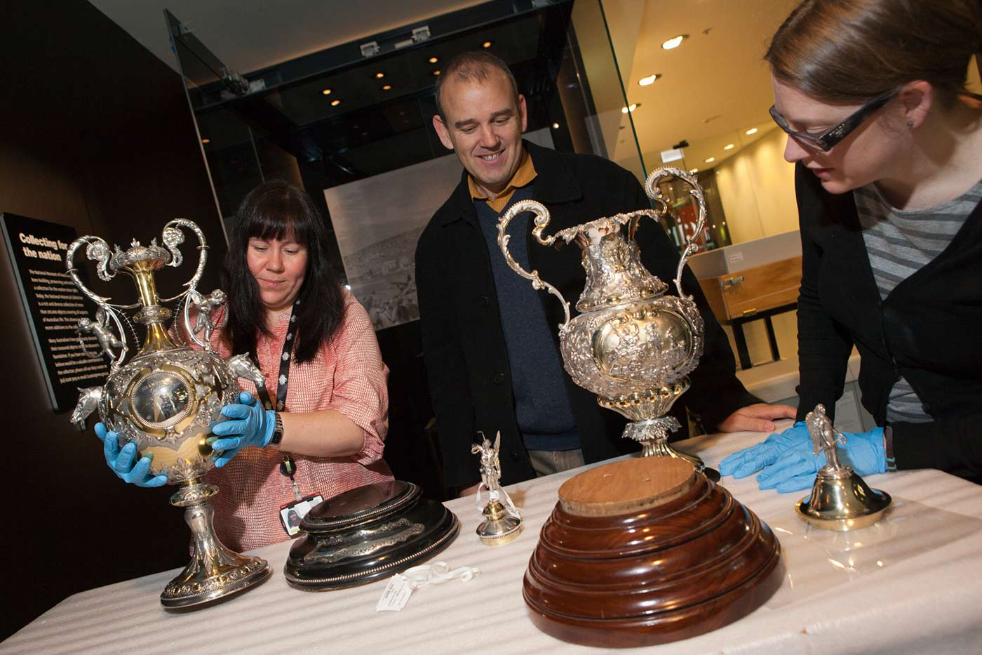Colour photograph of three people inspecting trophies.