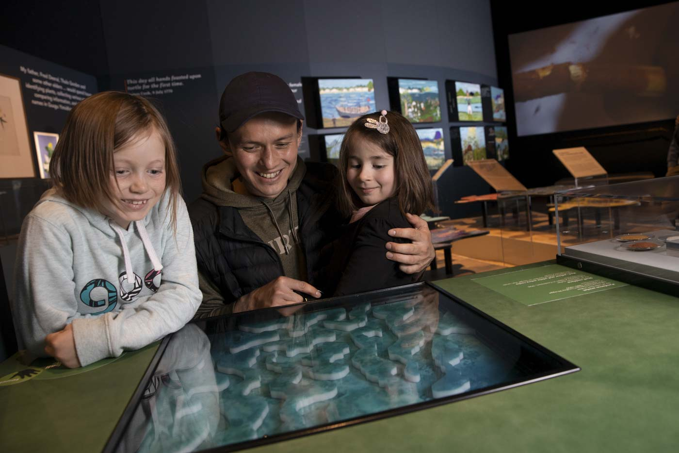 A man and two young girls behind a museum exhibit consisting of a blue-green reef puzzle. - click to view larger image