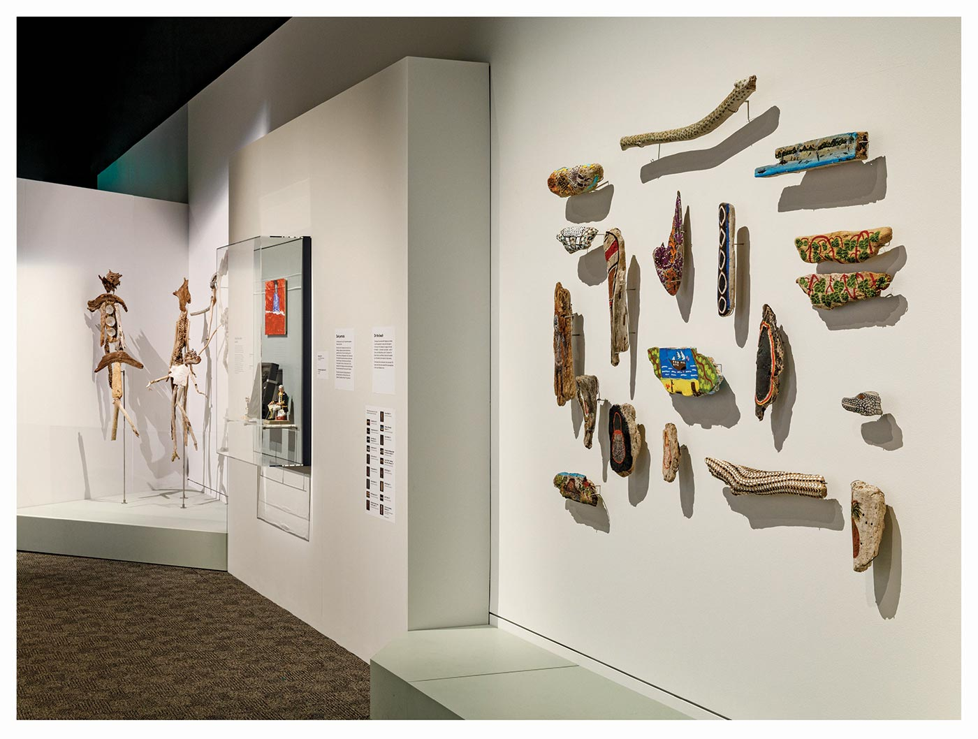 Sample page for the Endeavour Voyages: The Untold Stories of Cook and the First Australians catalogue. The page features images of an exhibition space with driftwood artwork mounted on the wall and on stands, and various other objects. - click to view larger image