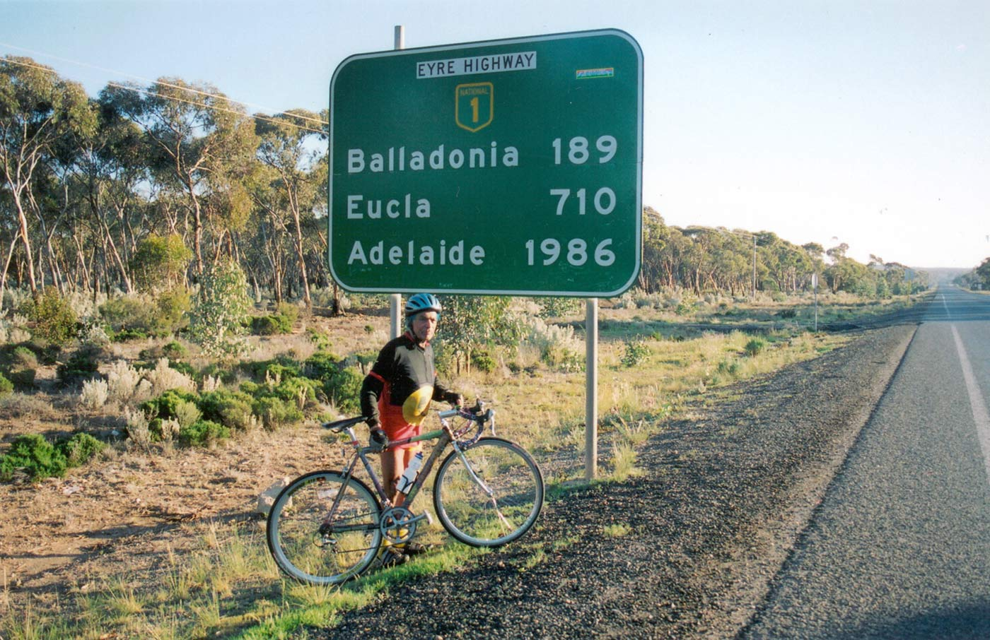 A colour photo of Alby Clarke on his bicycle at the start of the Nullabor Plain.  He is next to a road sign which reads: 'Eyre Highway, Balladonia 189, Eucla 710, Adelaide 1986. - click to view larger image