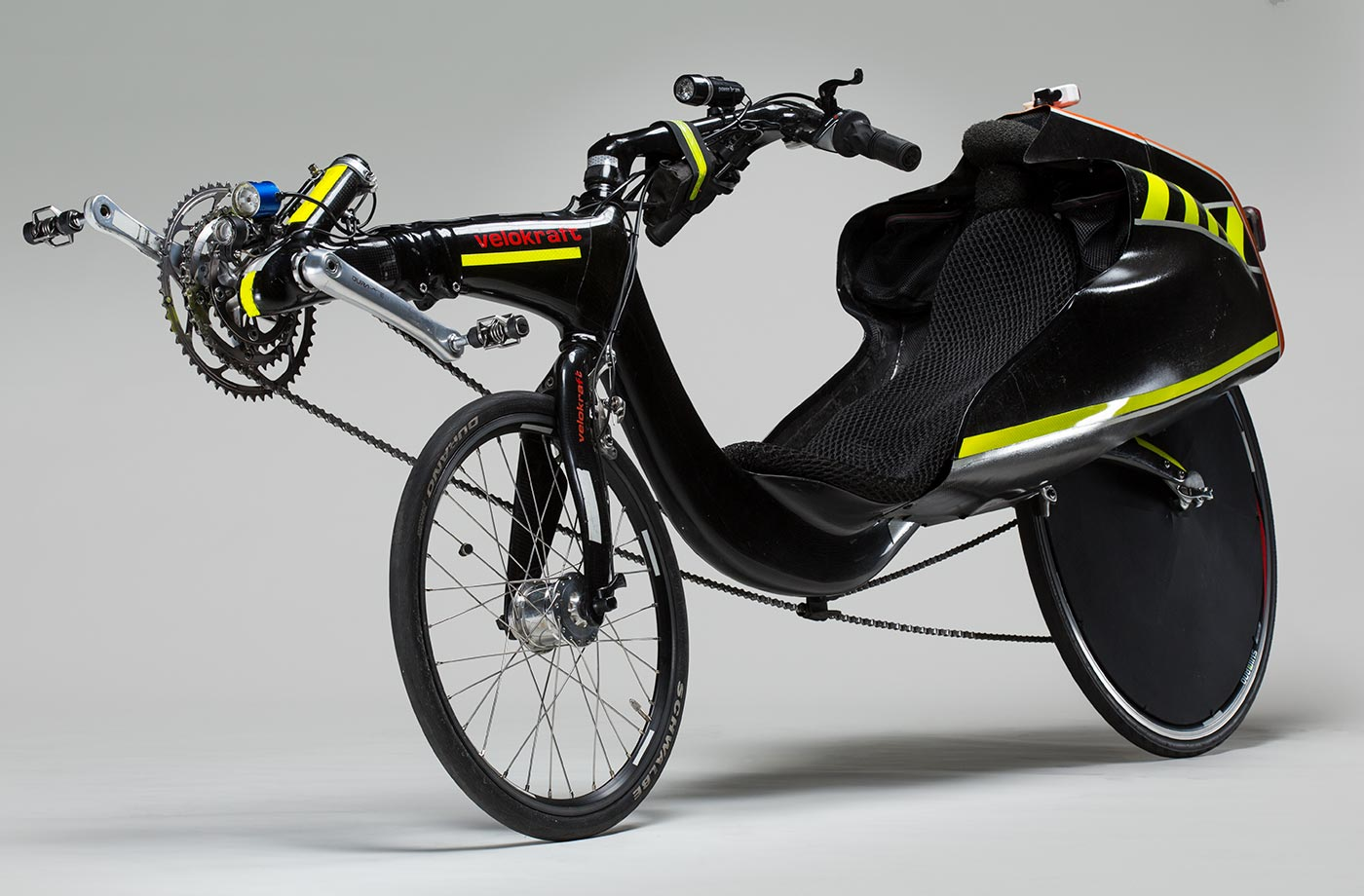 A recumbent bicycle with carbon fibre tailbox and two different size wheels. The rear wheel is larger and and has a black wheel cover. The pedals are in front of the front wheel. The steering is above seat. The body of the bicycle is black in colour with some bright yellow stripes. The text ' Velokraft ' is orange in colour and is printed on the frame in front of the bike. The orange colour is also on the top of the tailbox.  - click to view larger image