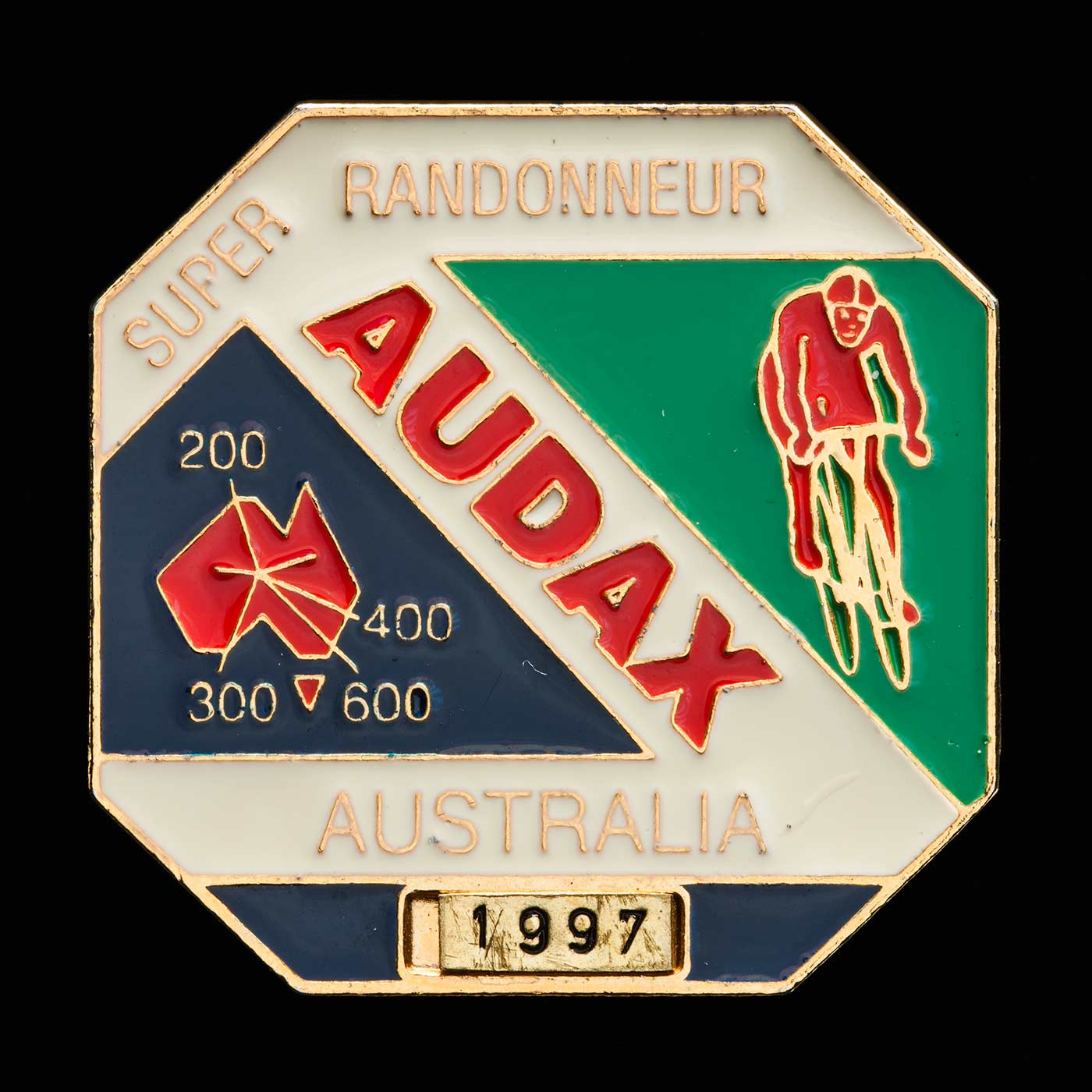 Red, green, white and blue medallion with an image of a cyclist at right and map of Australia at left. - click to view larger image