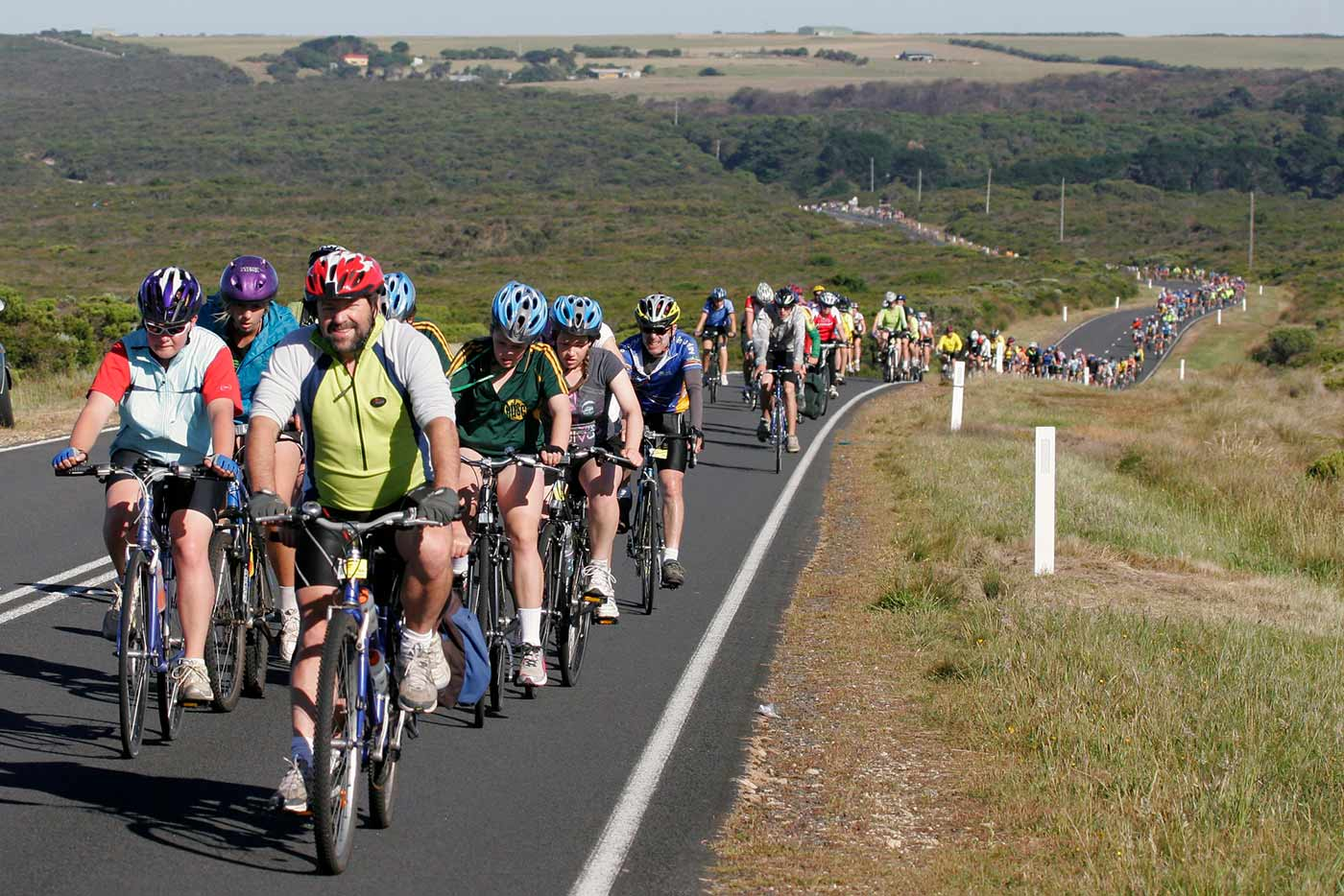 A group of cyclists on travelling along a road through countryside. - click to view larger image