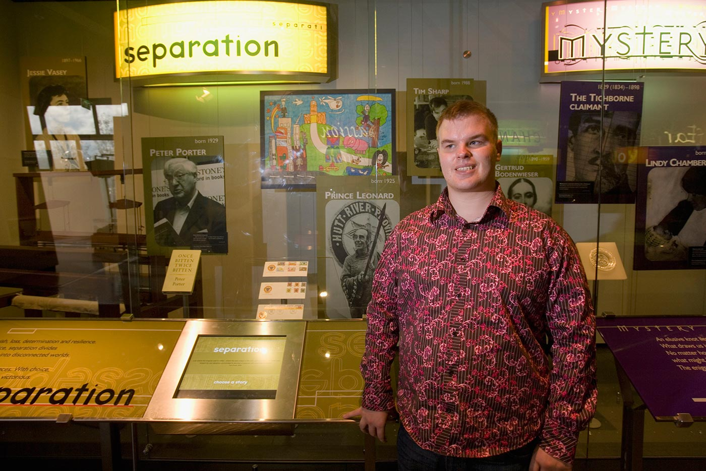 Young man in a patterned shirt, standing in front of a large glass exhibition display case - click to view larger image