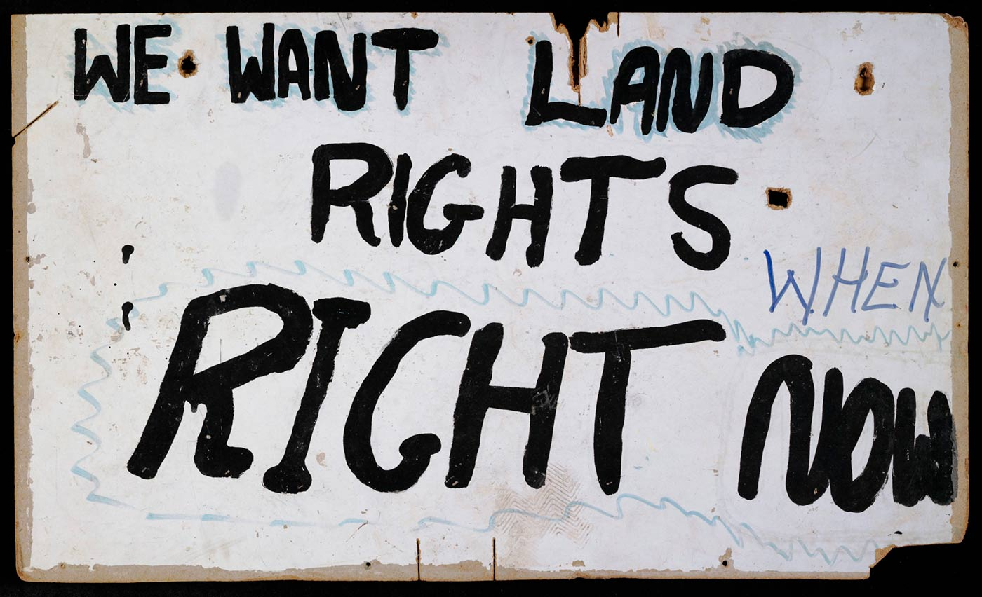 A political activist's placard. The text 'WE WANT LAND / RIGHTS / RIGHT NOW' has been painted in black paint on a rectangular masonite board, with a painted white background. 'WHEN' has been added in purple felt pen. 'WE WANT LAND' has a light blue wavy line border in felt pen. 'RIGHT NOW' is encircled by a wavy blue line in felt pen.