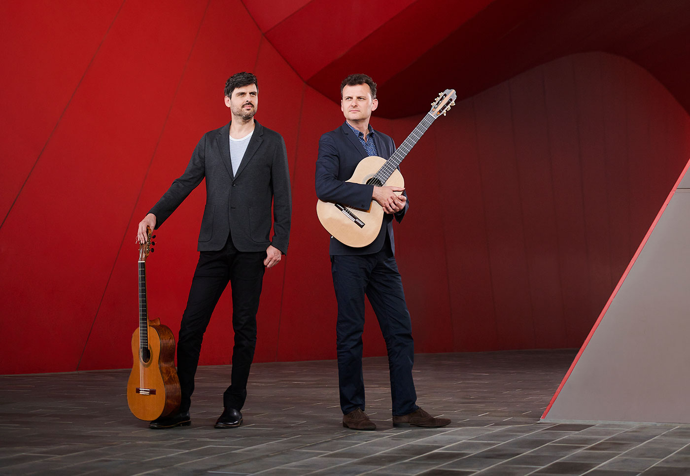 Slava and Leonard Grigoryan standing with instruments in the forecourt of the National Museum of Australia.