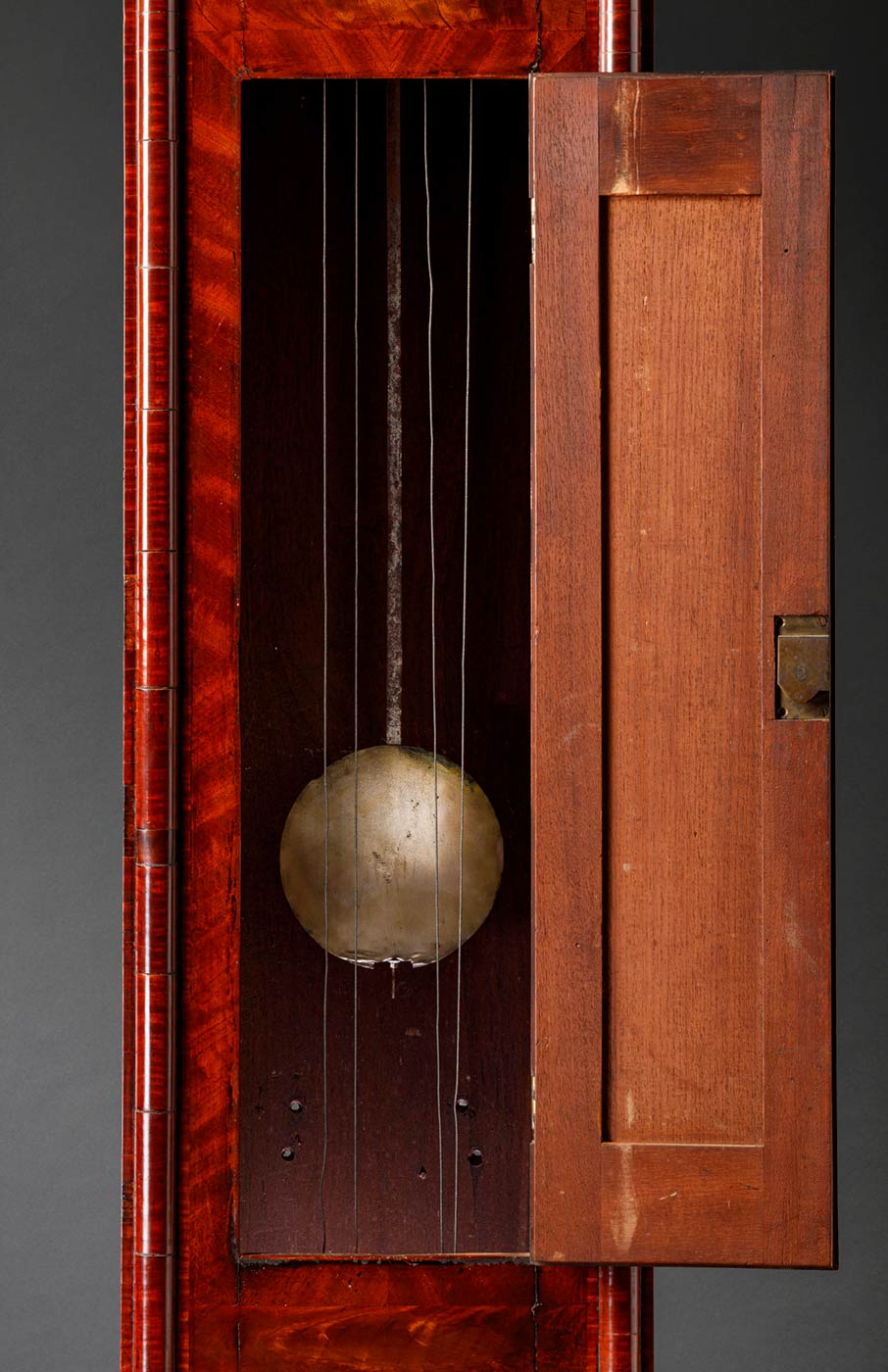Long case clock displaying pendulum section. - click to view larger image