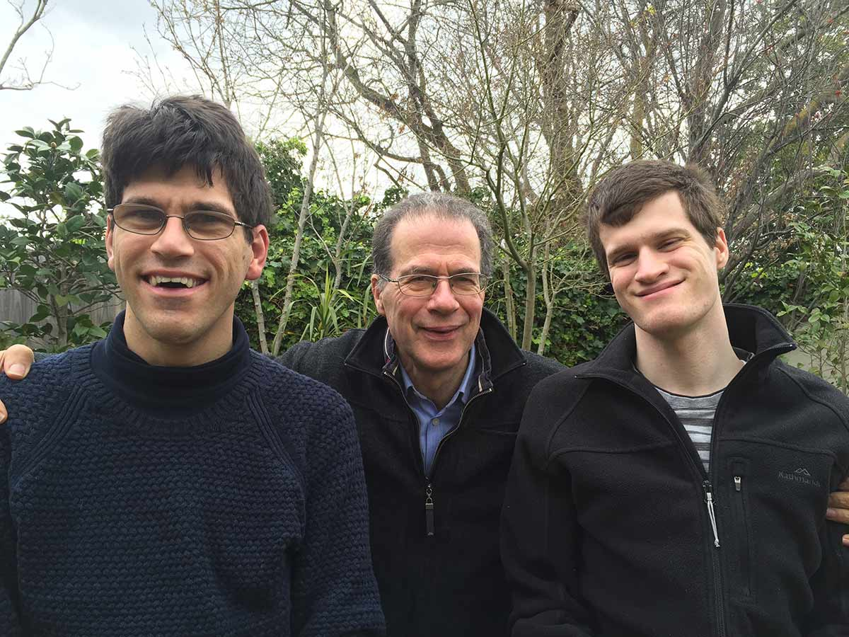 An older man and two younger men who are standing amongst a garden backdrop smile for the camera.