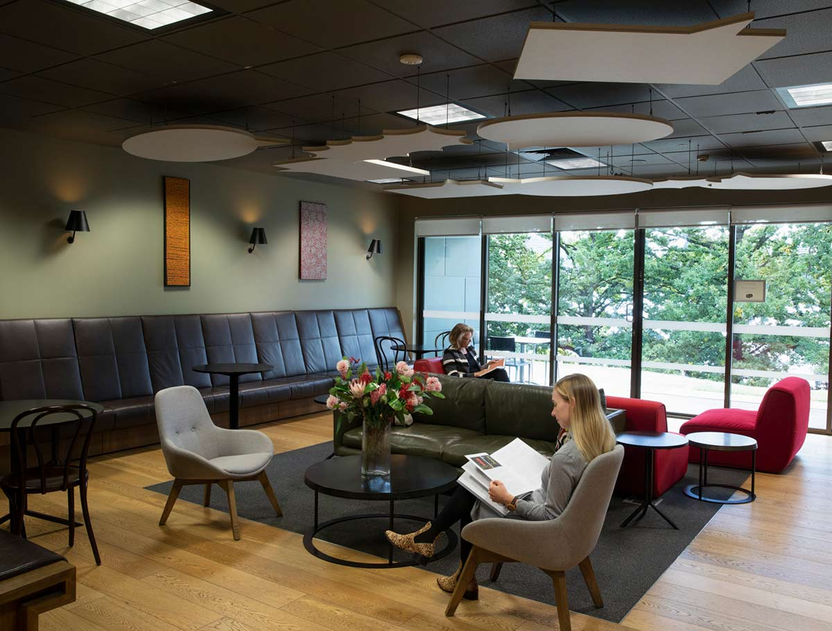 Visitors relaxing with reading material in a members lounge. - click to view larger image