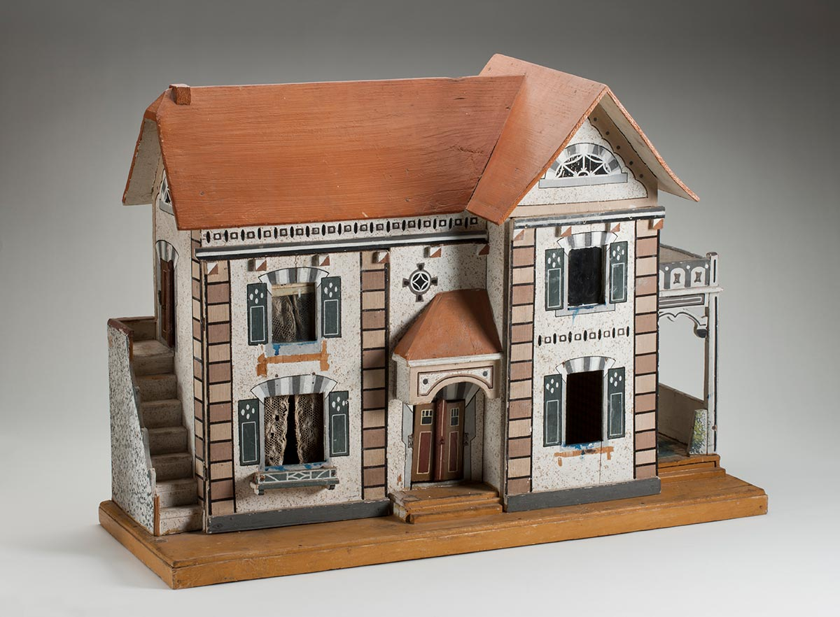A double storey dolls house with two panels at the front of the house that open to reveal the interior. It has a pitched brown roof, a set of stairs leading up to a door on the second floor on the left, a covered front entrance in the middle, and a covered porch on the right. It also includes lace curtains in top and bottom windows on the left panel. The exterior is decorated with painted gables, window coverings and stone effects above the windows and on the corners of the house. The double door main entrance on the front is finished with painted wooden strips representing lintels, sills, and architraves, and can be opened and closed. The house is secured to a wooden base. - click to view larger image