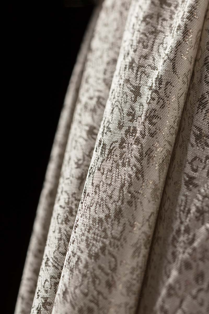 Cropped image of a cream-coloured synthetic brocade dress showing detailing on skirt. - click to view larger image