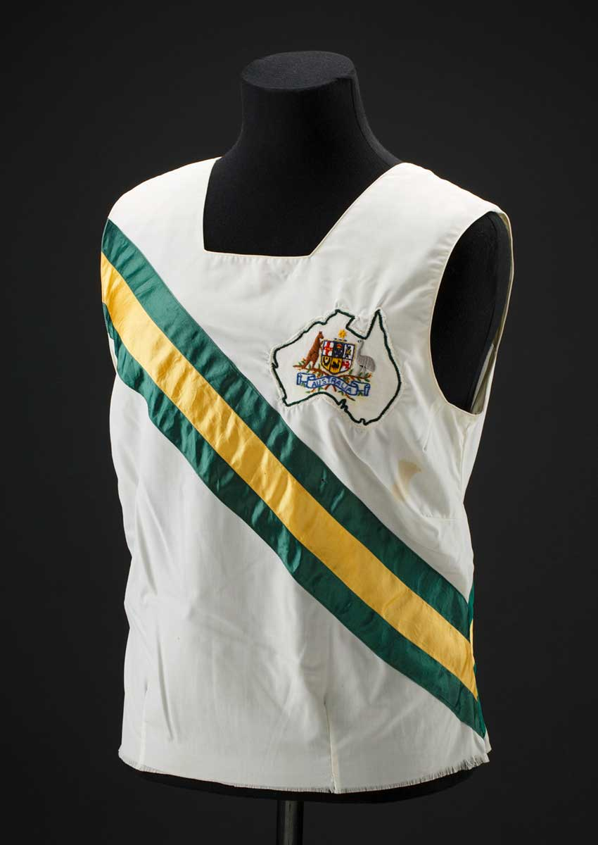 White singlet on a mannequin torso. The singlet has diagonal green and gold strips across the chest and the Australian coat of arms on the left breast. - click to view larger image