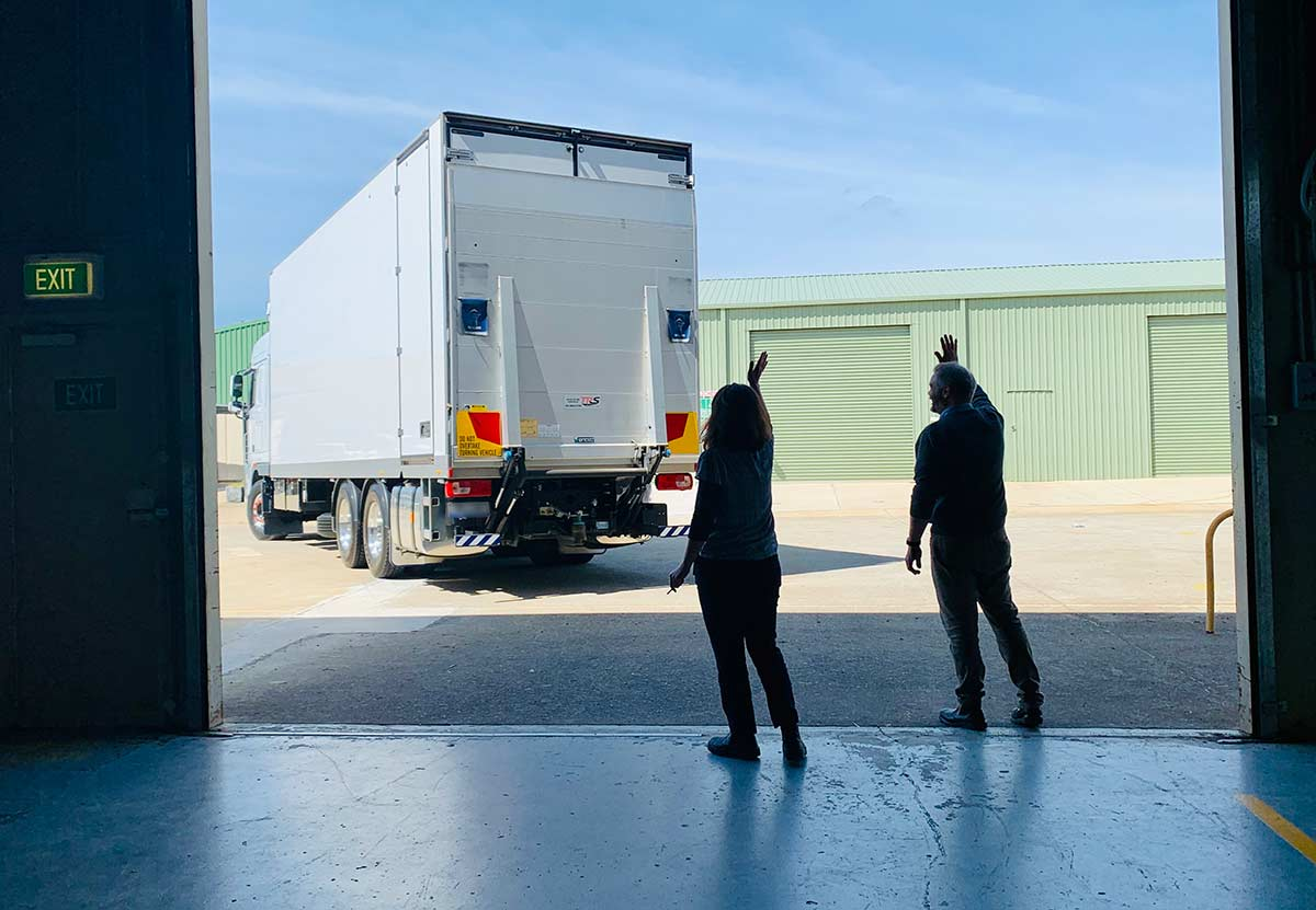 Two people wave off a truck that is leaving the depot.