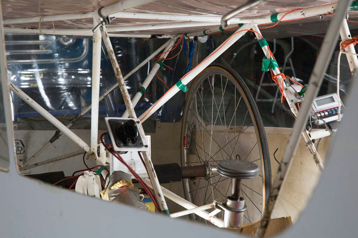 Close up of a solar-powered vehicle featuring bicycle fittings including wheels and frame to the interior. - click to view larger image
