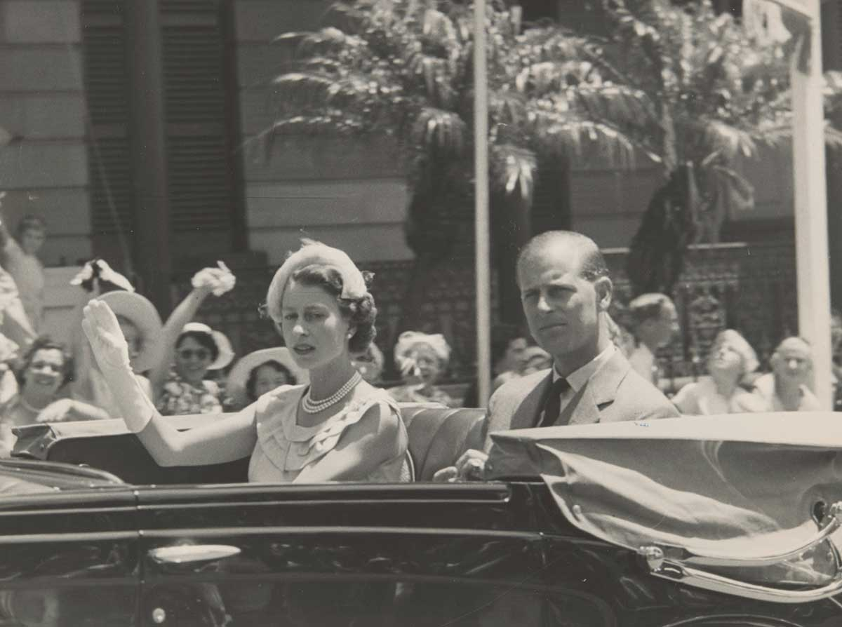 A black and white photograph of Queen Elizabeth II and His Royal Highness The Duke of Edinburgh, in an open car, waiving to the crowd on the street.