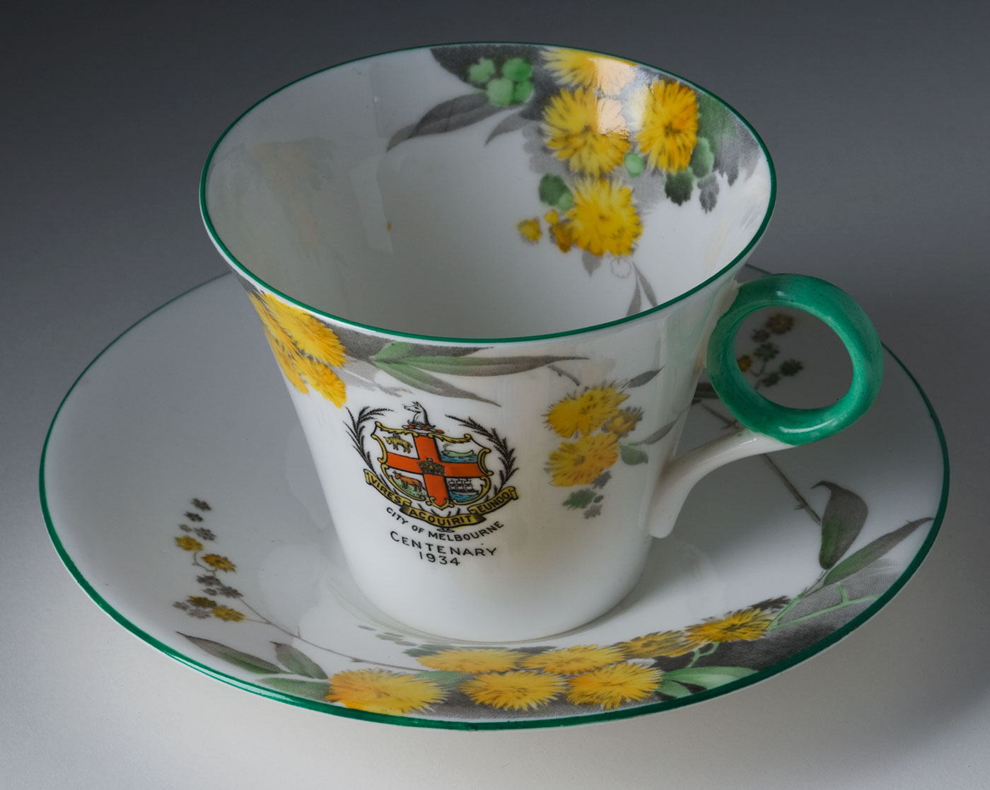 White china cup and saucer set painted with yellow wattle blossoms and pale green gum leaves. The 'City of Melbourne' emblem appears on the front of the cup with the words 'Centenary 1934'. The cup's handle is painted green. - click to view larger image