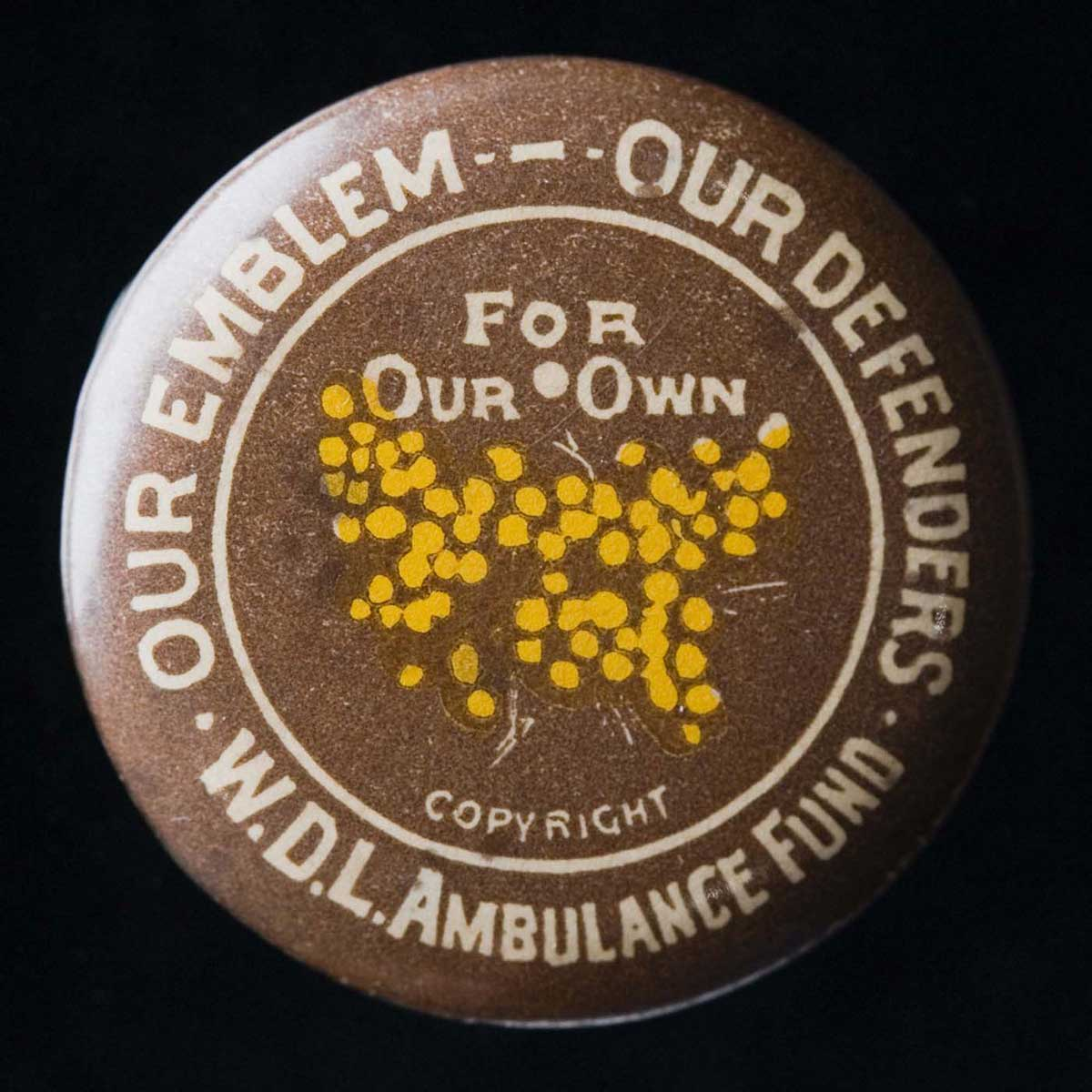 Brown-coloured circular badge with 'Our Emblem - Our Defenders, W.D.L Ambulance Fund' written around the border. Yellow wattle blossoms appear in the centre, along with the words 'For Our Own'. - click to view larger image
