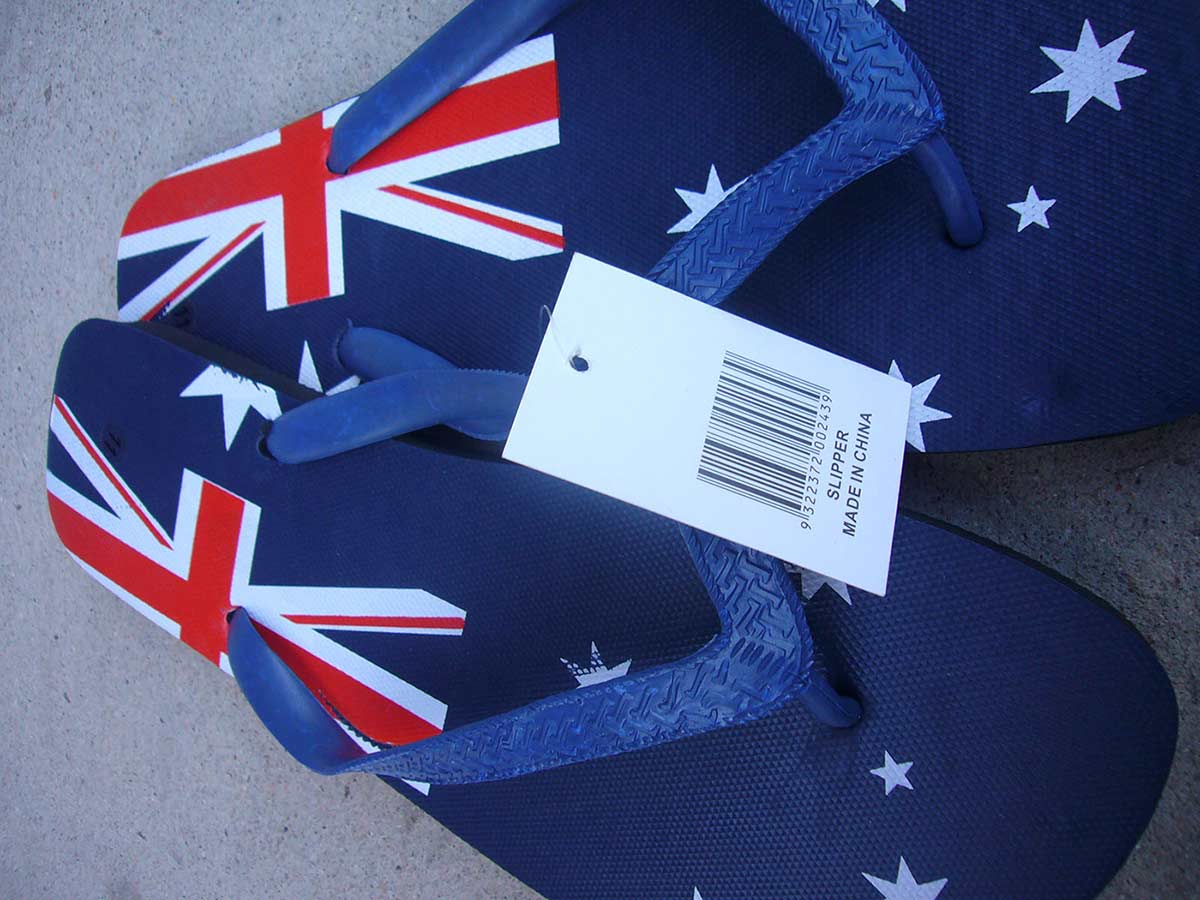 A colour photograph of a pair of blue rubber thongs which feature part of the Australian flag on the upper sole. A bar code tag attached to the thongs reads 'SLIPPER. MADE IN CHINA'. - click to view larger image