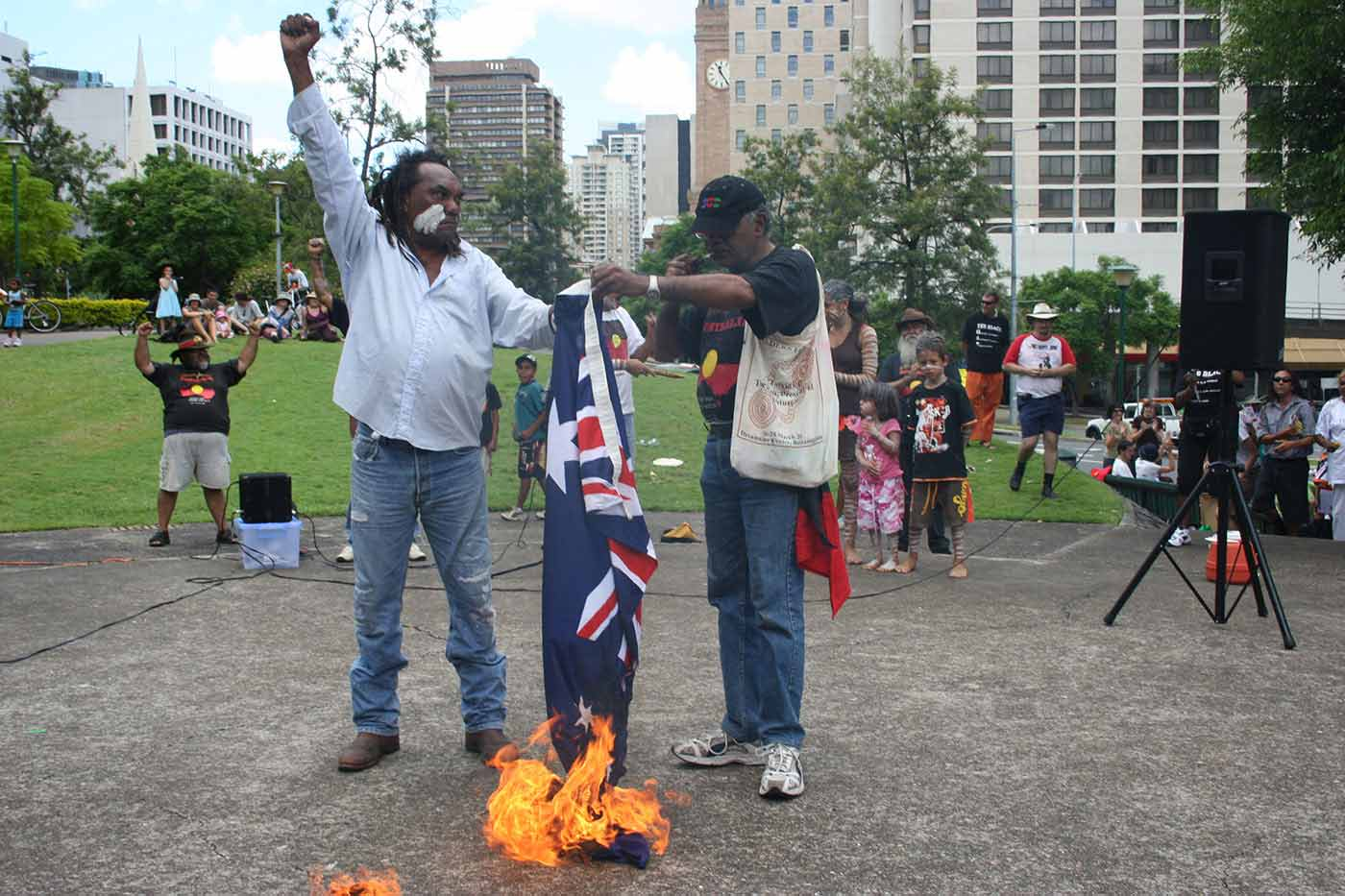 Colour photograph of two men holding the Australian flag over a fire while spectators look on. The man on the left has his right arm raised with closed fist. - click to view larger image