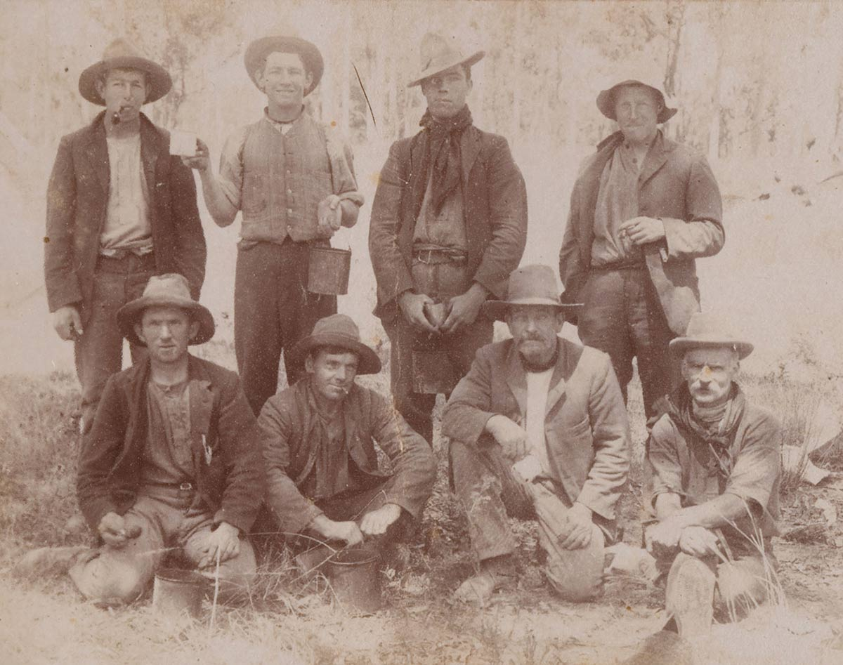 Postcard featuring a group of men in hats, many of whom are holding a billy or mug. - click to view larger image