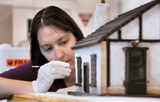 Conservator Cathy Collins preparing a 1930s doll's house for the Captivating and Curious exhibition.