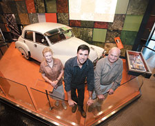 Visitors Audrey Healy and Albert Neuss with curator Daniel Oakman in front of the FJ Holden on display in the Nation gallery.