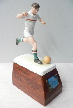 Ceramic figure of soccer player running up to kick a ball, with right leg on the ground and left leg extended backwards and bent at the knee. The painted figure wears a white uniform with a red and green vertical stripe across the chest, black boots and green socks with a red and white stripe. The figure is mounted on a wooden plinth with rectangular base and an engraved metal plaque at the front.