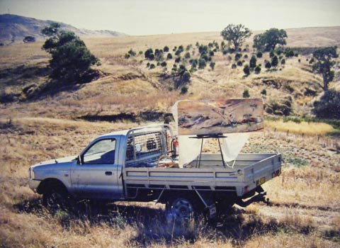 A silver utility vehicle with a tray back is parked in front of a creek bed, with trees and grasses in the distance. An easel supporting a landscape painting sits on the back of the ute.