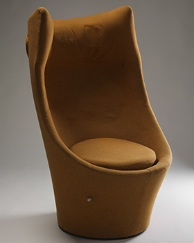 Upholstered orange chair with a circular base and cushion. The high back includes speakers in the winged headrest.