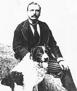 Black and white studio portrait showing a man seated on a hay bale, with a large two-toned dog sitting at his right knee.