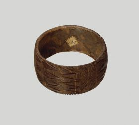 Bracelet made from the central strip of the hard coconut shell. A zigzag pattern has been cut into the outside, running all round in a repeat pattern.