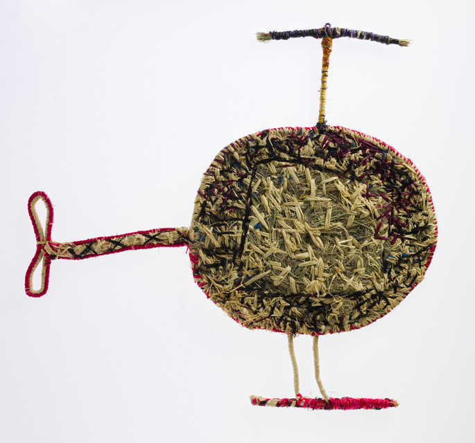 A sculpture depicting a helicopter. The sculpture is made of woven grass and plant material dyed in different colours.