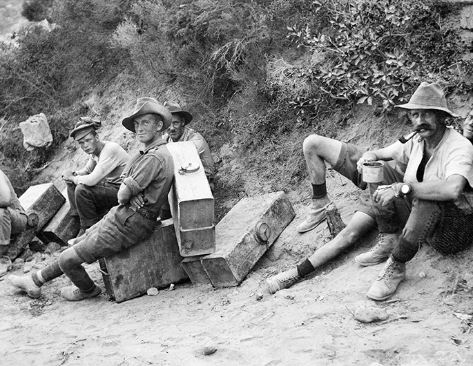 Black and white photo of a handful of Australian soldiers resting on or near their suitcase-sized water containers