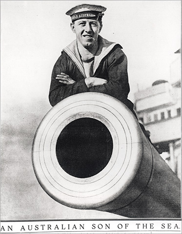 A sailor of the HMAS Australia poses on top of the battle-cruisers mighty guns.