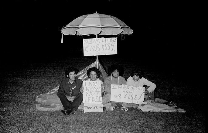 four young men sit in front of a beach umbrella at night holding up signs