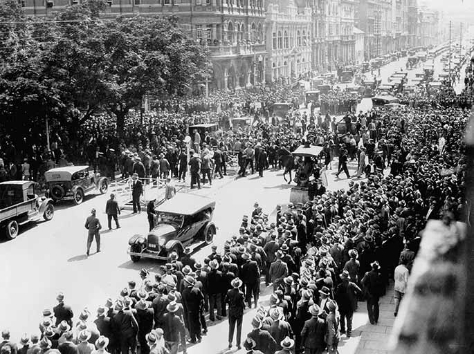 Photo taken from a second-storey window showing hundreds of men proceeding down a main street.