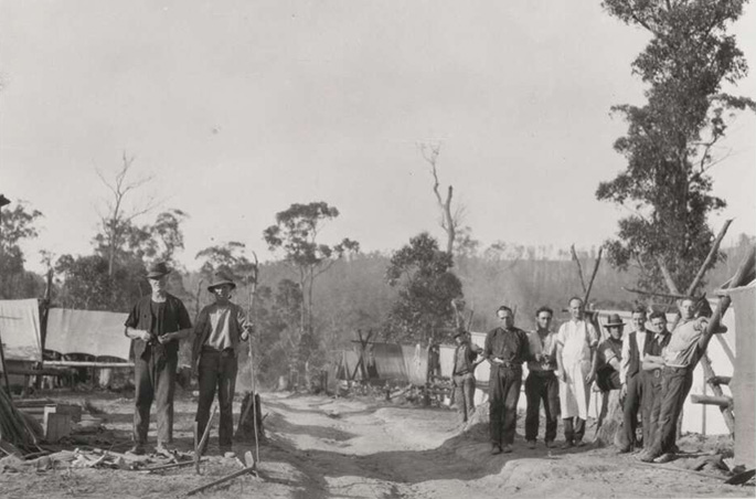 A group of 12 or so men in work clothes pose for the camera. They are in the bush on either side of a dirt track and surrounded by what appear to be tents. It's possible they're involved in land clearing.