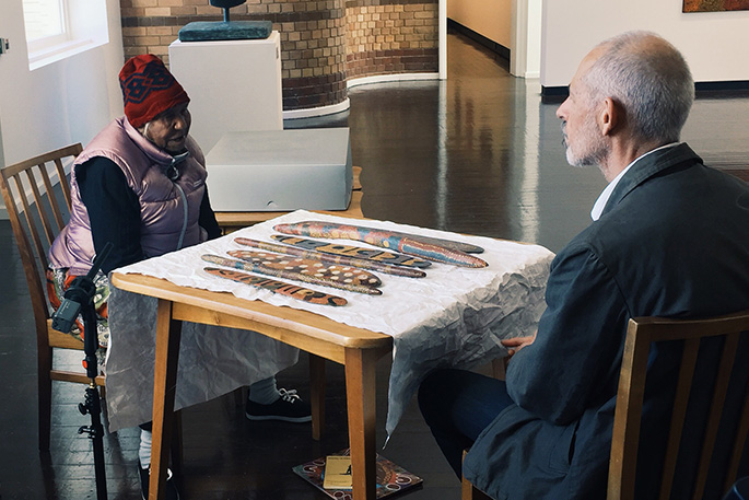Tilau Nangala and Senior Curator Peter Thorley sitting at a table which has Aboriginal artworks laid on top of it.